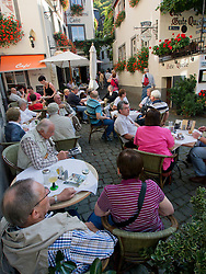 `Tourists sitting in cafe in  historic village of Beilstein  in Mosel Valley Rhineland Germany