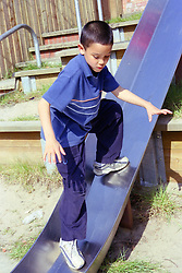 Young boy playing on slide in children's playground,