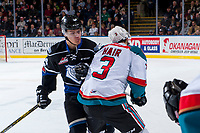 KELOWNA, CANADA - DECEMBER 30: Kaid Oliver #34 of the Victoria Royals checks Kelvin Hair #3 of the Kelowna Rockets in front of the bench during second period on December 30, 2017 at Prospera Place in Kelowna, British Columbia, Canada.  (Photo by Marissa Baecker/Shoot the Breeze)  *** Local Caption ***