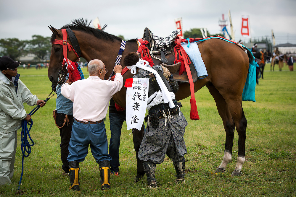 """MINAMISOMA, JAPAN - JULY 24 :  A samurai horsemen prepares their horse during the Soma Nomaoi festival at Hibarigahara field on Sunday, July 24, 2016 in Minamisoma, Fukushima Prefecture, Japan. """"Soma-Nomaoi"""" is a three day traditional festival that recreates a samurai battle scene from more than 1,000 years ago. The festival has gathered more than thousands visitors as Fukushima still continues to recovery from the 2011 nuclear disaster, the samurai warriors battles for recovery of the area. (Photo: Richard Atrero de Guzman/NURPhoto)"""