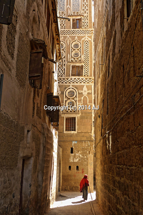Elderly person walking through narrow lane in old Sanaa