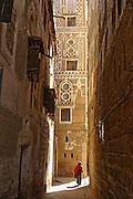 Elderly person walking through narrow lane in old Sanaa