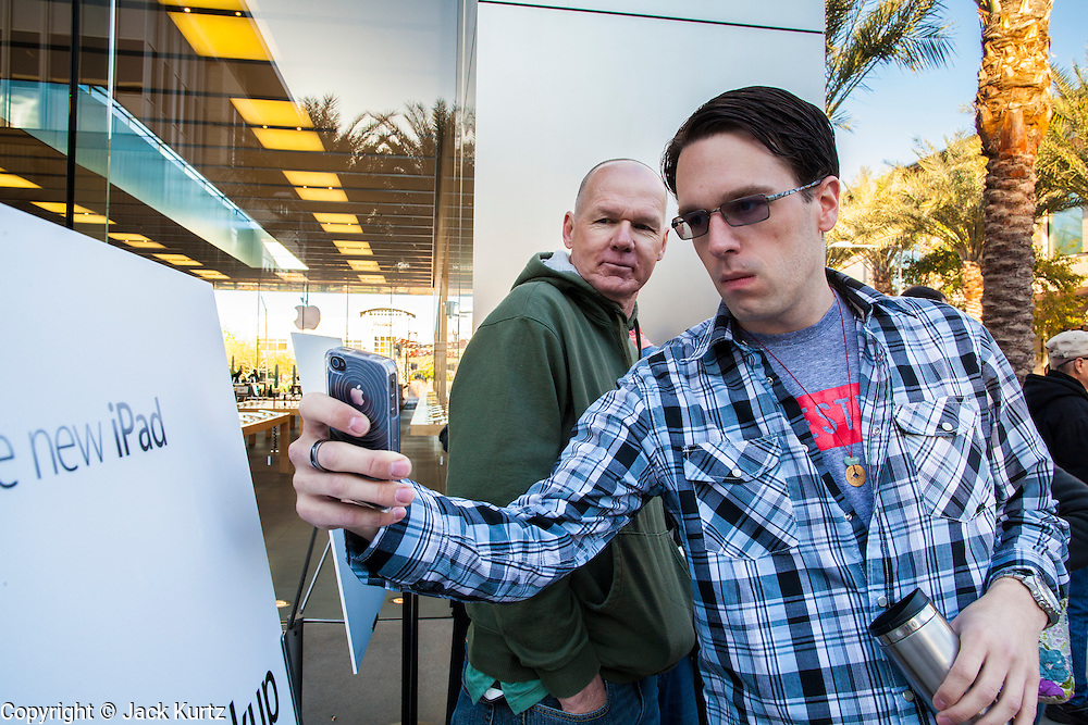 16 MARCH 2012 - SCOTTSDALE, AZ:  JORDON LOW, from Phoenix, AZ, takes a picture of the New iPad sign with his iPhone at the Apple Store in Scottsdale. Several hundred people were in line at the Apple Store in the Scottsdale Quarter in Scottsdale, AZ, Friday to buy the New iPad.    PHOTO BY JACK KURTZ