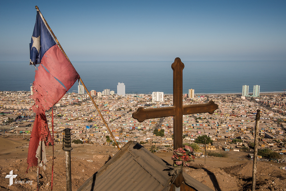 A cross affixed to a roadside memorial joins a tattered Chilean flag on a road overlooking Iquique, Chile, on Wednesday, April 23, 2014. A magnitude 8.2 earthquake on April 1, 2014, struck approximately 95km northwest of Iquique, condemning several thousand houses and severely damaging more than 10,000 others.  LCMS Communications/Erik M. Lunsford