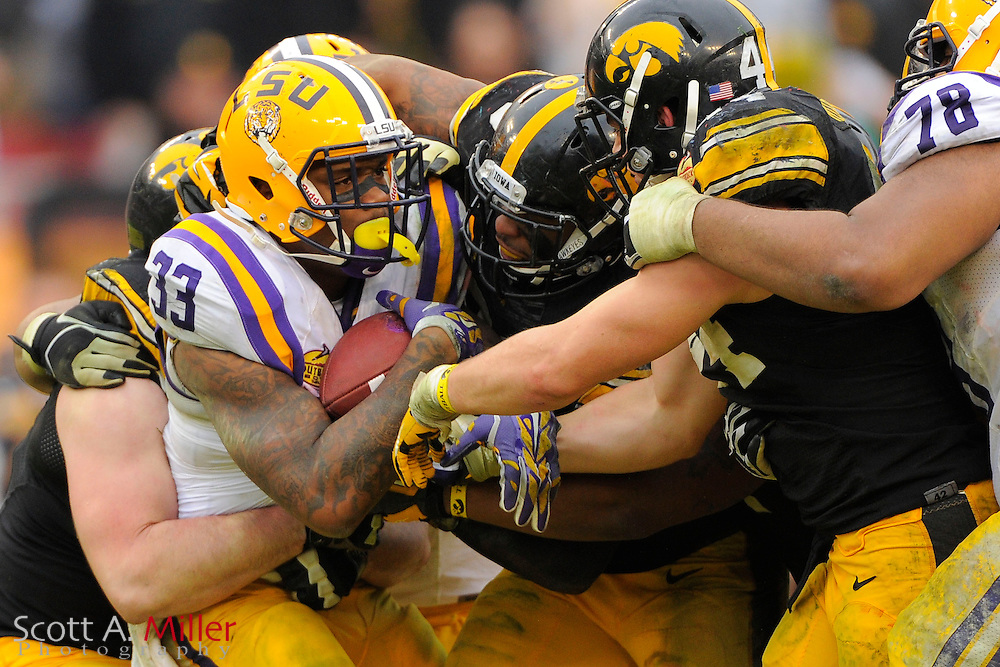 LSU Tigers running back Jeremy Hill (33) is tackled by Iowa Hawkeyes linebacker Christian Kirksey (20) and linebacker James Morris (44) during LSU's 21-14 win in the 2014 Outback Bowl at Raymond James Stadium on Jan 1, 2014  in Tampa, Florida.            ©2014 Scott A. Miller