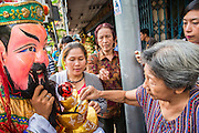 14 OCTOBER 2012 - BANGKOK, THAILAND:People make donations to a diety during a procession on the first day of the Vegetarian Festival in Bangkok's Chinatown. The Vegetarian Festival is celebrated throughout Thailand. It is the Thai version of the The Nine Emperor Gods Festival, a nine-day Taoist celebration beginning on the eve of 9th lunar month of the Chinese calendar. During a period of nine days, those who are participating in the festival dress all in white and abstain from eating meat, poultry, seafood, and dairy products. Vendors and proprietors of restaurants indicate that vegetarian food is for sale by putting a yellow flag out with Thai characters for meatless written on it in red.    PHOTO BY JACK KURTZ