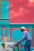 An ice cream vendor pushes his cart past a colorful wall along the Plaza Principal in Dolores Hidalgo, Guanajuato, Mexico. Miguel Hildago was a parish priest who issued the now world famous Grito - a call to arms for Mexican independence from Spain.