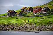 Couple walking in Kirkjub¯ur, Faroe Islands