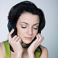 portrait of a young woman listening music on isolated background
