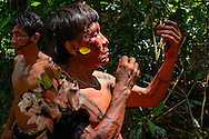 Yanomami preparing his painting outside the village for the welcoming party.