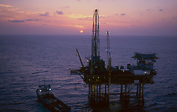 Stock photo of an offshore jack-up drilling rig with crewboat at sunset.
