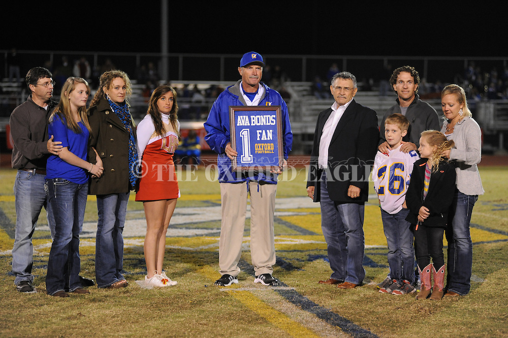 Oxford High coach Johnny Hill (center) presents a memento to the family of former Oxford High teacher Ava Bonds at halftime of Oxford High vs. Saltillo in Oxford, Miss. on Friday, October 19, 2012. Oxford won to improve to 9-0.