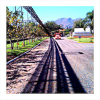 A truck approaches, driving through the Herradura tequila distillery grounds in Tequila, Jalisco, Mexico. The large pipes overhead cast a shadow on the road. These pipes carry tequila from one part of the distillery to another. (iPhone image) --- Image created for http://tastetequila.com