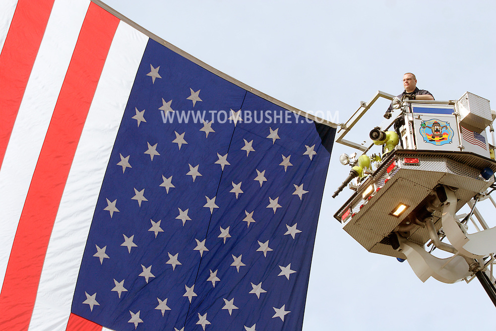 Middletown, NY - A firefighter in a ladder truck help hang a large American flag between his truck and another fire engine on the route of a Memorial Day parade on May 25, 2009.