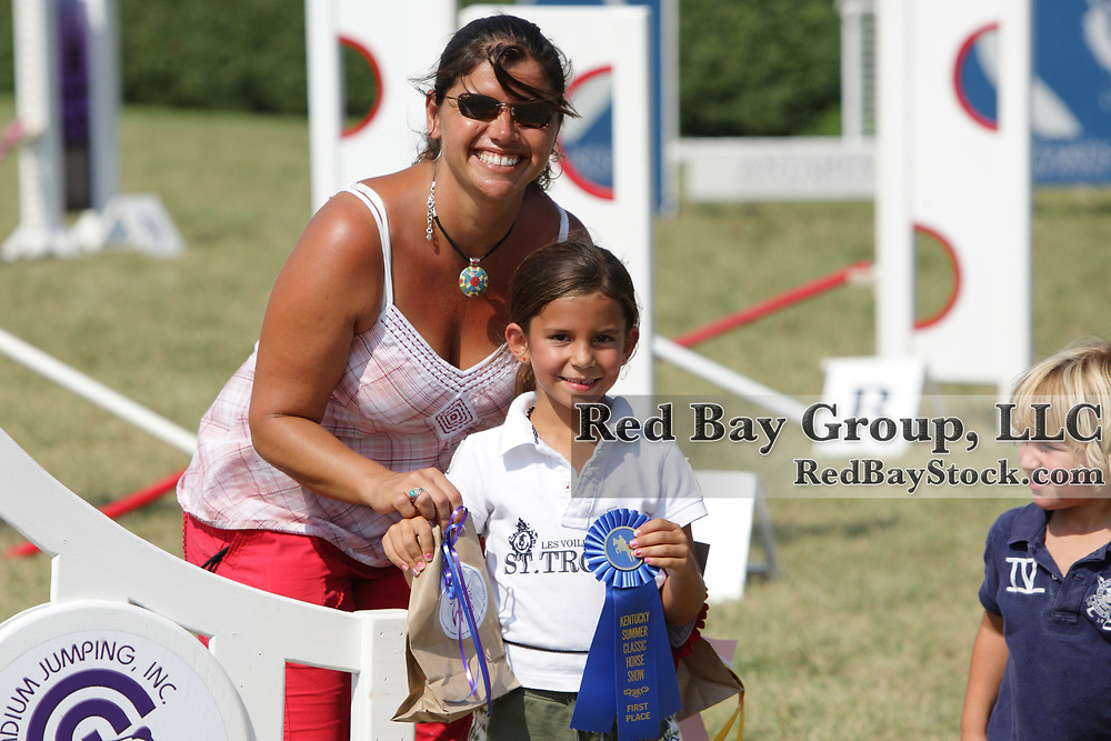 Jessica Newman, JWI Executive Director presenting an award to Reid Arani at the Just World International Horseless Horse Show held during the Kentucky Summer Classic at the Kenucky Horse Park.