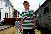 A young Scottish lad in his Celtic top clutching a mobile phone in a garden, Aberdeen, Scotland, UK 2004