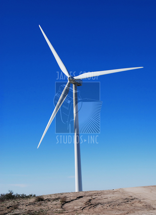 A giant wind turbine against the deep blue sky