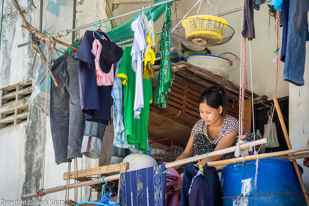 30 APRIL 2013 - MAHACHAI, SAMUT SAKHON, THAILAND: A Burmese woman hangs laundry on a tenement balcony above a fish processing plant in Mahachai, Samut Sakhon province, Thailand. The Thai fishing industry is heavily reliant on Burmese and Cambodian migrants. Burmese migrants crew many of the fishing boats that sail out of Samut Sakhon and staff many of the fish processing plants in Samut Sakhon, about 45 miles south of Bangkok. Migrants pay as much $700 (US) each to be smuggled from the Burmese border to Samut Sakhon for jobs that pay less than $5.00 (US) per day. There have also been reports that some Burmese workers are abused and held in slavery like conditions in the Thai fishing industry.         PHOTO BY JACK KURTZ