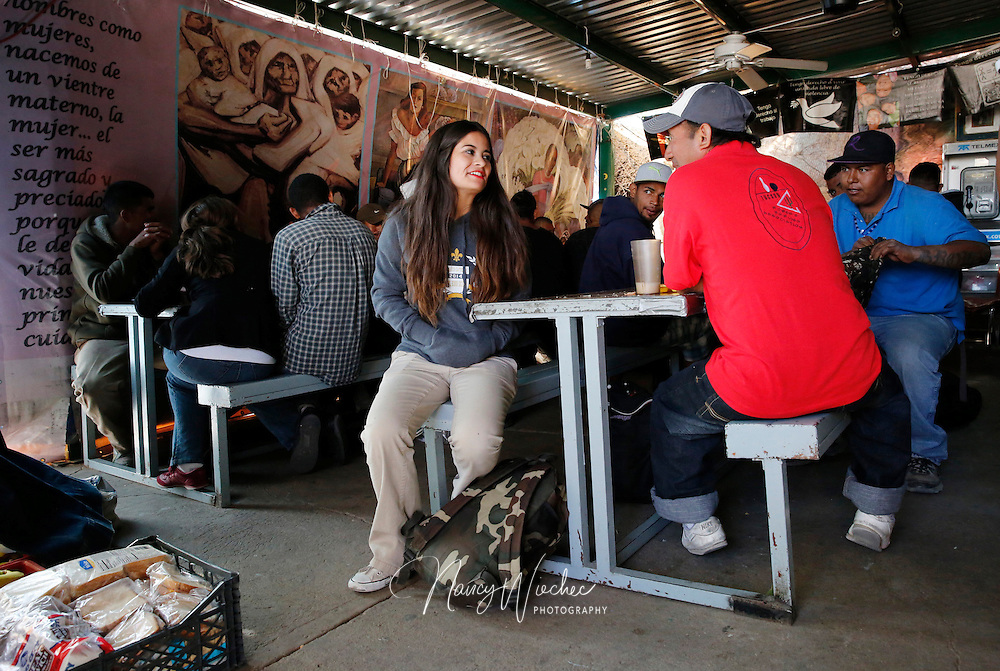 "Kino Teen Nicole Davison sits down to chat with men after they finished dinner at the ""comedor,"" the kitchen and dinning hall of the ""Centro de Atencion al Migrante Deportado,"" the Aid Center for Deported Migrants, in Nogales, Sonora. (Photo taken April 2, 2014) (Photo by Nancy Wiechec)"