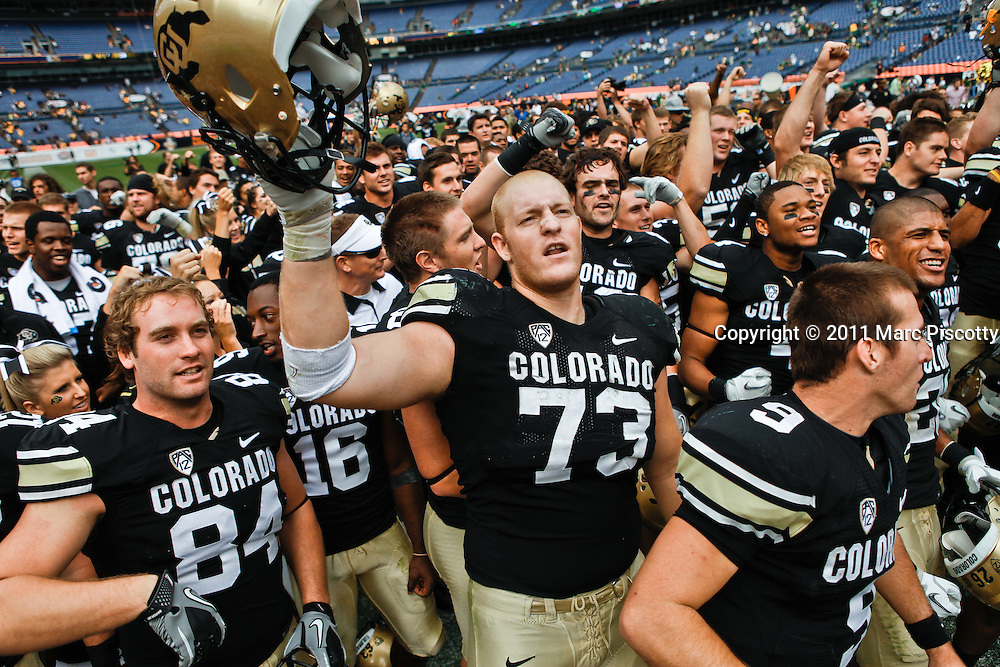 SHOT 9/17/11 2:59:51 PM - Colorado's Ryan Miller #73 sings the Colorado fight song with teammates after beating Colorado State  during the Mile High Showdown game at Sports Authority Field at Mile High Stadium. Colorado won the in-state rivalry game 28-14. (Photo by Marc Piscotty /  © 2011)