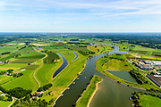 Nederland, Gelderland, Gemeente Voorst, 17-07-2017; De Voorster Klei, gezien naar het noorden, Deventer aan de verre horizon. In het kader van het programma Ruimte voor de Rivier is de bandijk in de voorgrond verlaagd. Bij hoogwater kan het water nu ook via de uiterwaarden stromen, langs de nieuwe dijk (links van de waterplassen).<br /> NOOT: Zie ook opnames van de oorspronkelijke situatie.<br /> Voorster 'clay' seen to the north, Deventer on the distant horizon. A new dike has been build, more inland and the first part of the existing dike (bottom) is  reduced in height, creating 'more space for the river'. <br /> See also recordings of the original situation.<br /> luchtfoto (toeslag op standard tarieven);<br /> aerial photo (additional fee required);<br /> copyright foto/photo Siebe Swart