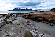 The stunningly beautiful Isle of Rum from the Valtos Sandstone Formation, Laig Bay, Isle of Eigg under a dramatic, stormy sky.<br /> <br /> The Rum peaks are from left to right: Sgurr nan Gillean, Ainshval, Trollabhal (Trollaval), Bienn nan Stac, Askival & Hallival (Allival).<br /> <br /> Date taken: 12 June 2016.