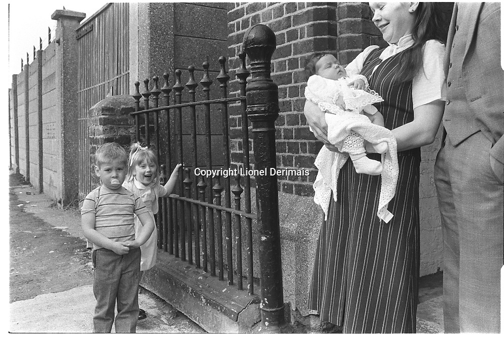 Babe in his / her mother's arms at christening, Isle of Dogs, London street photography in 1982. Tri-X