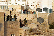 Israeli special forces search the rooftops of Palestinian homes surrounding the Jewish community in Hebron. Approximately 600 Jewish settlers live in the historic center of the city which has a Palestinian population of more than 160,000.<br /> Hebron, Israel. 08/11/2007
