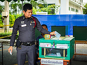 07 AUGUST 2016 - BANGKOK, THAILAND: A Thai policeman drops his ballot into a ballot box at a polling place at Wat That Thong in Bangkok. Thais voted Sunday in the referendum to approve a new charter (constitution) for Thailand. The new charter was written by a government appointed panel after the military coup that deposed the elected civilian government in May, 2014. The charter referendum is the first country wide election since the coup.      PHOTO BY JACK KURTZ