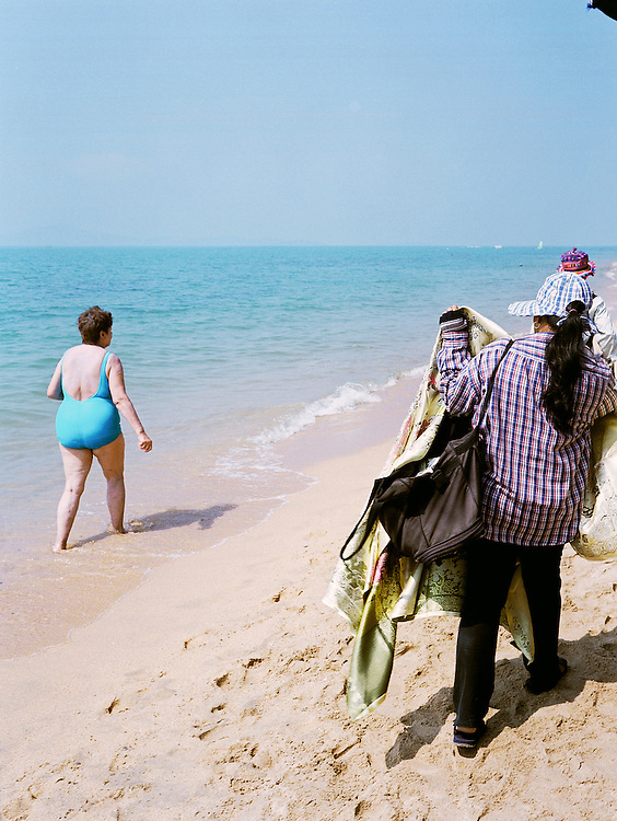 A Thai vendor pursues a tourist down the beach to show off her wares.