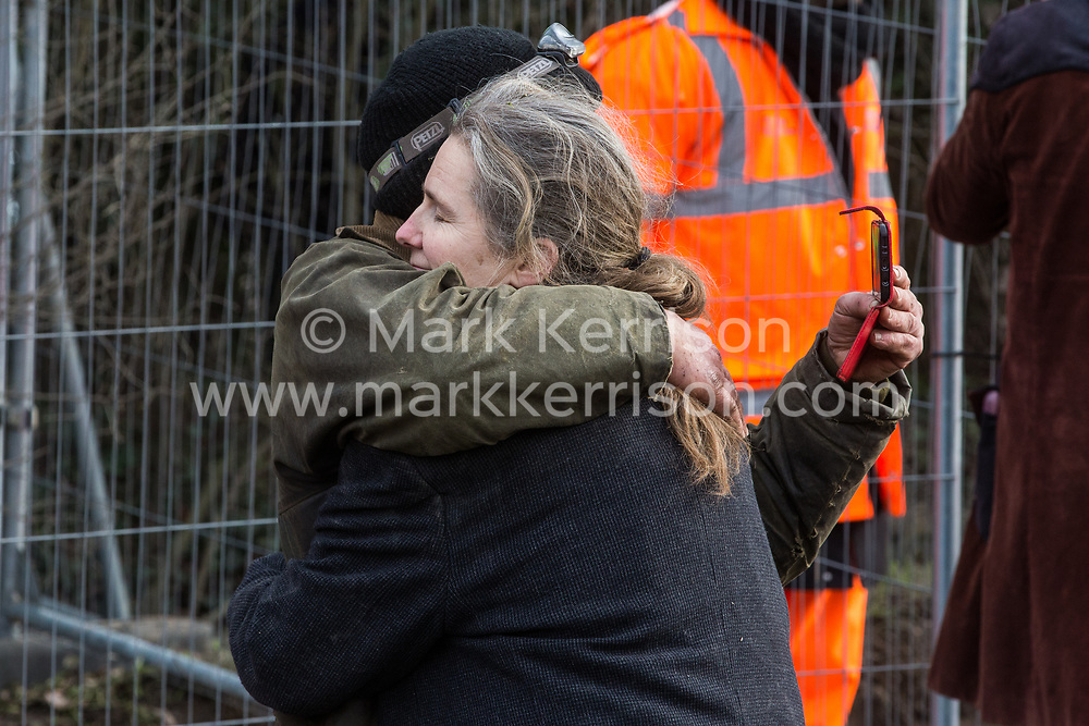 Harefield, UK. 8 February, 2020. An environmental activist embraces Mark Keir of Save the Colne Valley on Harvil Road during action to prevent tree felling works for the HS2 high-speed rail link in the Colne Valley.  The activists, based at a series of wildlife protection camps in the area, prevented the tree felling, for which road and rail closures had been implemented, for the duration of the weekend for which it had been scheduled.