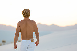 back of a shirtless blond man walking in White Sands, NM