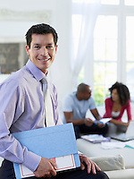 Business man holding document folder in living room couple sitting in background