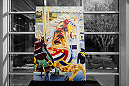 Garden City, New York, USA. March 9, 2019.  After the Unveiling Ceremony of painting of closeup of Nunley's Carousel lead horse, artist Michael White's mural (approximately 7 feet high by 5 feet wide) is on display for the rest of the event in the carousel pavilion, on Museum Row on Long Island.  (Background digitally desaturated)