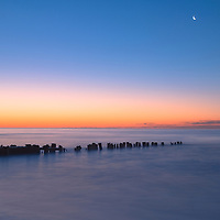 The crescent moon shines bright during sunrise at Folly Beach, South Carolina.