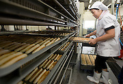 Staff at Oizen Shoten loads trays of freshly baked sasa-kamaboko at the company's factory in Tome City, Miyagi Prefecture, Japan on 11 Sept. 2012.  Photographer: Robert Gilhooly