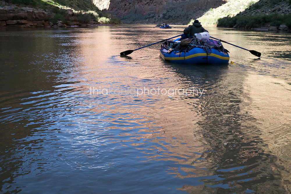 Reflections of Grand Canyon with oar raft on Colorado River, AZ