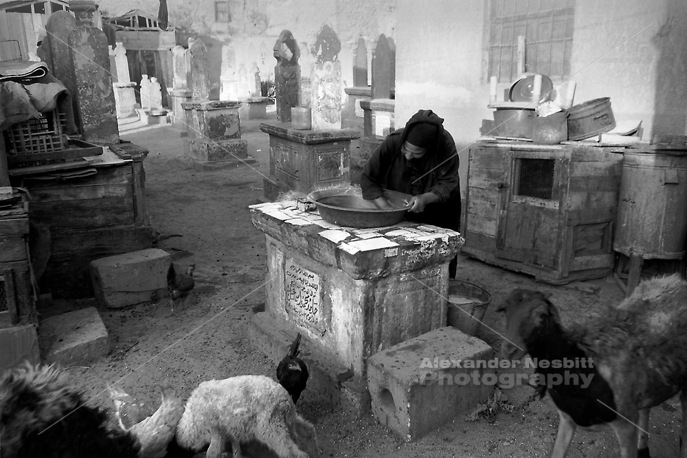 City of the Dead, Cairo, 2000 - Mother cleans a pot on top of a grave marker near her make shift kitchen..