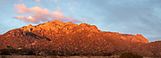 """The setting sun reflects its rays on the Sandia """"Watermelon' Mountains"""