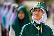 11 JULY 2013 - PATTANI, PATTANI, THAILAND:   Students at the Bantaladnadklongkud School in Pattani watch the Thai flag go up in the morning. There are 108 students at Bantaladnadklongkud School and they are all Muslims. Five of the school's eight teachers are Buddhists.    PHOTO BY JACK KURTZ