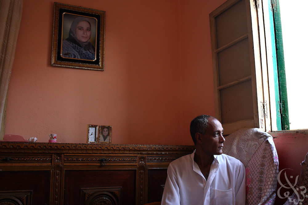 Hamid  Khalil, 46, sits near a portrait of his late wife, Amal al Dusouqi, 43, in their apartment in Mahalet Damana, 135 kilometers north of Cairo. Khalil's wife died April 9, 2008, after being trampled in a subsidized bread line stampede near her home. Rising food prices have become a increasing  crisis for Egypt's poor over the past several months.