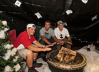 "Seniors David MacDonald, Kris Shepard and Jamie Gill take the chill off of ""Winter"" as they set up their winter hallway on Thursday evening for Gilford High School's Four Seasons themed Homecoming.  (Karen Bobotas/for the Laconia Daily Sun)"