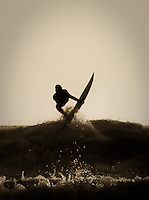 A surfer is silhouetted in action at Kuta Beach, Bali, Indonesia, Southeast Asia.