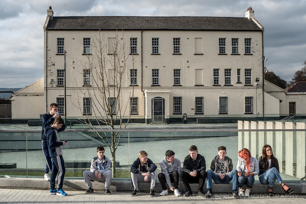 A group of Derry teenagers hang out in the afternoon sun. Younger generations don't have personal memories of the Troubles of the past decades.