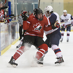 WELLINGTON, - Dec 11, 2015 -  Exhibition Game 2- Team USA vs Team Canada East at the 2015 World Junior A Challenge at the Wellington District Community Centre, ON. Brett Murray #17 of Team Canada East takes the hit from Grant Jozefek #15 of Team United States during the first period.<br /> (Photo: Andy Corneau / OJHL Images)