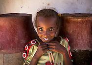 Smiling Sudanese girl in front of water jars in Gunfal, Sudan.