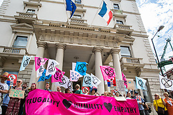 London, UK. 5 July, 2019. Climate activists from Extinction Rebellion protest behind a 'Frugality. Humility. Empathy.' banner outside the French embassy in solidarity with members of Extinction Rebellion France who were pepper-sprayed at short range by French police after they occupied the Pont de Sully in central Paris to call for more government action and media attention on climate change.