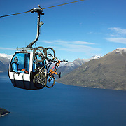 Mountain bikers ride the Skyline scenic gondola to the Queenstown Mountain Bike track on Ben Lomond above  Queenstown..Queenstown is nestled on the shores of the crystal clear waters of Lake Wakatipu in the Central Otago region of the South Island of New Zealand..Queenstown is New Zealand's premier tourist destination providing an abundance of year round outdoor activities for both young and old. Queenstown, Central Otago, South Island, New Zealand. 18th May 2011. Photo Tim Clayton..