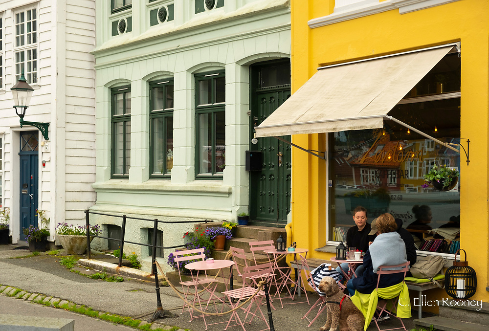 People sitting with their dog at an outdoor cafe in the Nordness section of Bergen, Vestlandet, Norway