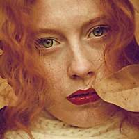 Close-up portrait of female youth with red curly hair and piercing green eyes, surrounded by autumn leaves.